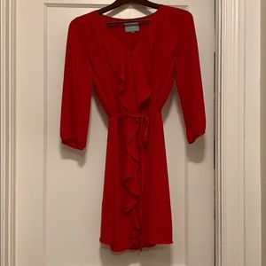 Red shift dress with front ruffle and tie.